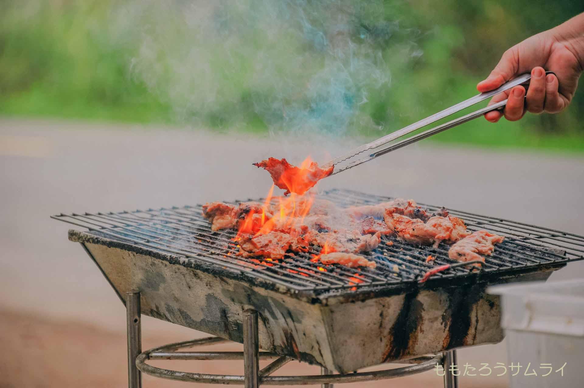 外でコンロを使い肉を焼いている画像